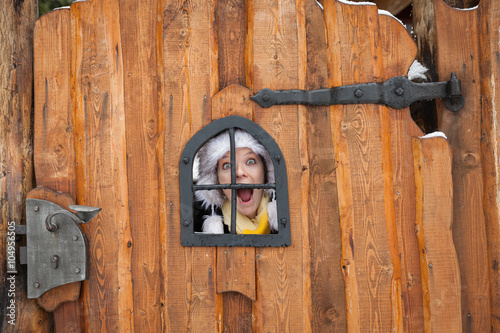 Young Lady Is Looking Through A Window In A Wooden Gate Buy This