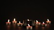 Group of burning candles in the dark with elegant reflections. Static shot.