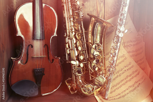 Fotografie, Obraz  Musical instruments: saxophone, violin and flute with notes on wooden background