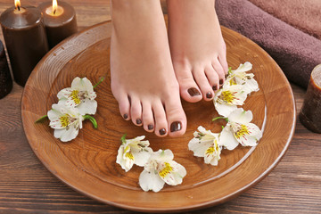 Obraz na płótnie Canvas Manicured female feet in spa wooden bowl with flowers and water closeup