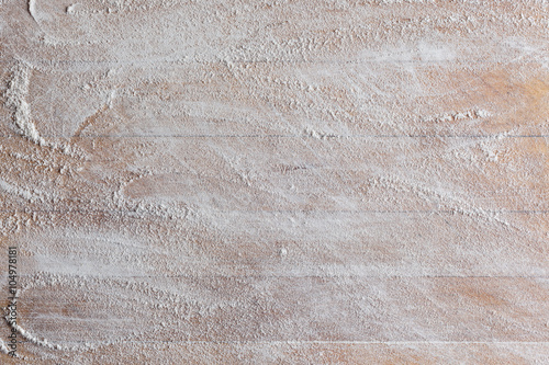 Leinwand Poster Rough wooden rectangular used cutting board background with flour directly from