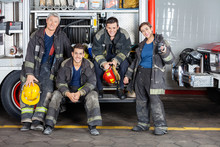 Portrait Of Confident Firefighters By Truck