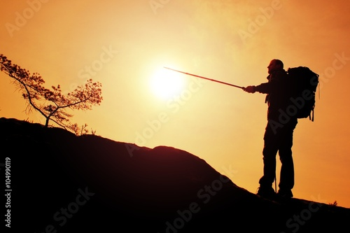 Tourist guide show the right way with pole in hand  Hiker with