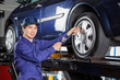 Mechanic Filling Air Into Car Tire At Garage
