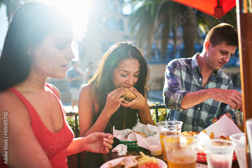Poster Kruidenierswinkel woman eating big burger together with friends at outdoor restaurant