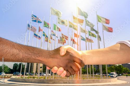 Fotografia Multiracial handshake with world flags background - Black and white men hand sha