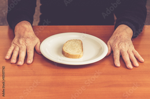 Valokuva  Old man's hands on table with one slice of bread in middle