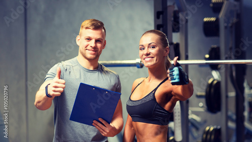 Fototapeta smiling young woman with personal trainer in gym
