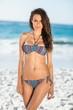 Serious pretty brunette posing in bikini