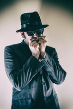 Bluesman Playing Harmonica. Man In Suit, Hat And Sunglasses Playing A Harmonica.