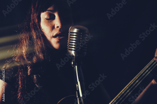 Pretty Woman Singing with Guitar. Attractive female playing an electric guitar and singing into a vintage microphone. Set in dark room with spot lighting and edited with vintage effects. - 105065323