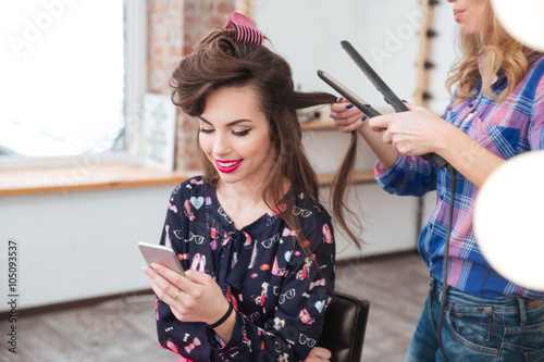 Obraz na plátně  Hairdresser applying straightener for long hair of smiling  woman