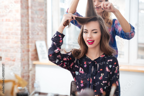 Fotografie, Obraz  Female hairdresser brushing hair of smiling woman