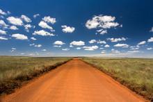 Rural Orange Dirt Road With Blue Sky And Far Horizon