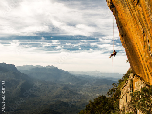 Photo Stands Mountaineering Abseiling a negative yellow rock wall with mountains on backgrou