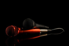 Two Microphones Lying On Black Surface. Black Background, Close Up