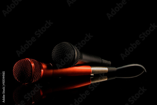 Photo  Two microphones lying on black surface