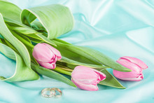 Two Rings And Tulips On A Turquoise Background