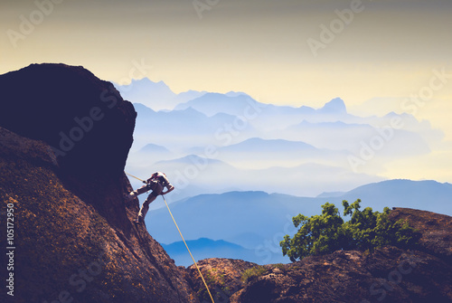 Climber against mountain valley Canvas Print