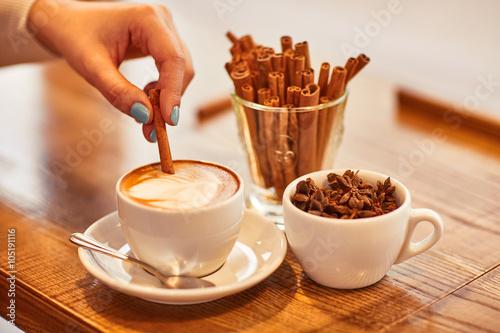 Fototapeta Pleasant woman putting cinnamon  into cup of coffee obraz