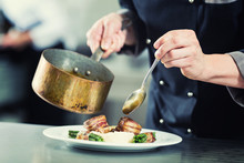 Chef Pouring Sauce On Dish In Restaurant Kitchen