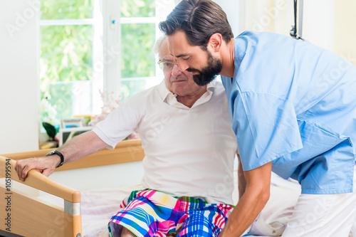 Fotografia  Altenpfleger hilft älterem Mann aus Rollstuhl ins Bett