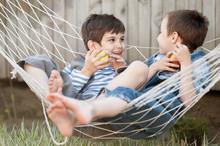 Children Eat Apples In A Hammock