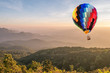 Colorful hot air balloon over mountain at sunset