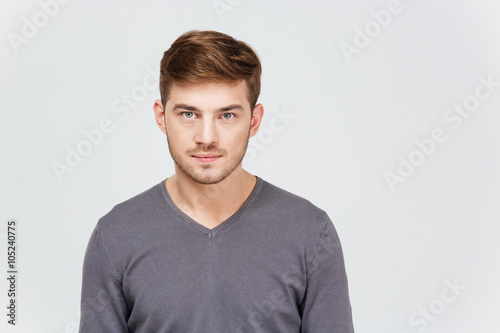 fototapeta na lodówkę Portrait of serious handsome young man in grey pullover