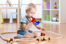 Child Playing With Wooden Railway On The Floor In Nursery. Little Boy Plays A Pipe Imagining The Train Driver That Gives A Beep