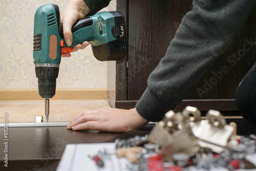 Fotografie, Obraz  Assembling furniture from chipboard, using a cordless screwdriver