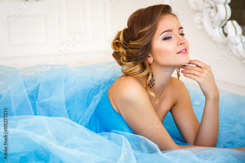 Fotografia Beautiful bride lying on gorgeous blue dress Cinderella style in a morning