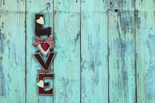 Country L-O-V-E Sign Hanging On Rustic Teal Blue Background