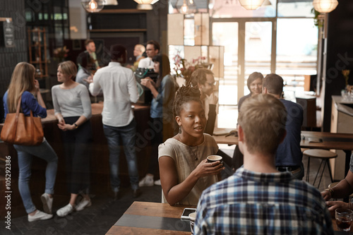 Fotografía  African woman talking with friend inside busy coffee shop