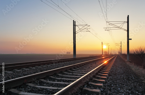 Fotomural Railroad - Railway at sunset with sun