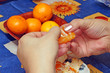 The woman cleans tangerines on a blue cloth