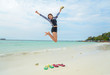 Portrait of young pretty woman jumping on the beach, relaxing