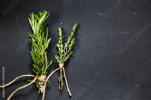 Valokuva Rosemary and thyme bounds on a dark grey board