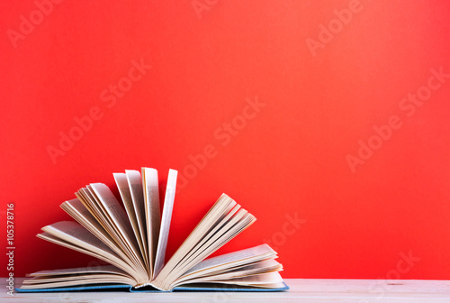 Photographie  Open hardback book on wooden deck table and red background