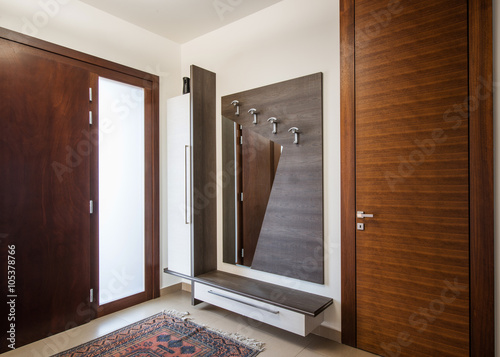 Foto  Hallway interior with wooden hanger and mirror