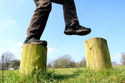 Fotografie, Obraz  Man walking on wooden stepping stones