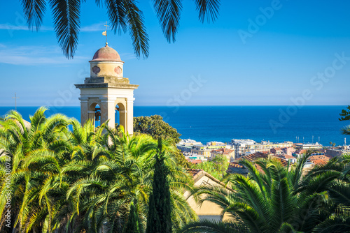 In de dag Liguria the belfry and church's roof is hiding behind the palms, sanremo, italy