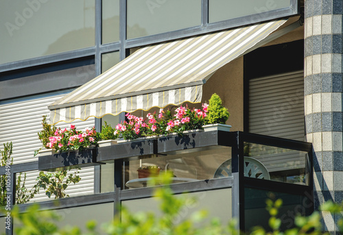 Fotografie, Obraz  Balcony with awning opened and beautiful flowers - covered by sun-shield on a wa