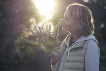 Girl Smelling The Fragrance Of A Rosemary Twig At Sunset In The Middle Of The Forest. Aroma Of Wild Plant In A Quiet Place