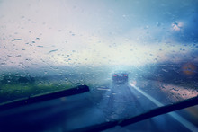 Dangerous Vehicle Driving In The Heavy Rainy And Slippery Road. Raindrops On Windshield Of Moving Car On Highway. Abstract Blurred Bad Weather Vehicle Driving.