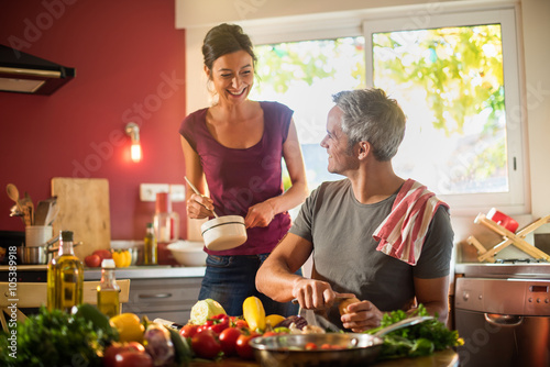 Crédence de cuisine en verre imprimé Cuisine Trendy couple cooking vegetables from the market in the kitchen