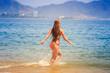 blonde slim girl in bikini runs into sea splashes against hills