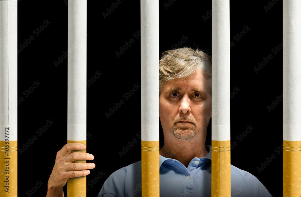 Ein Mann ist hinter einem Gefängnis von Zigaretten darstellen ...