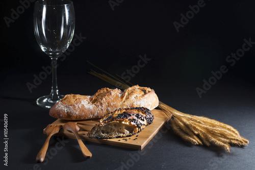 In de dag Bakkerij Fresh bread , wheat and empty wine glass on wooden and black bac