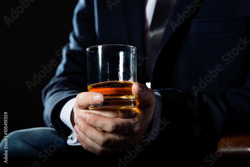 Fotografia, Obraz Closeup of serious businessman holding  glass of whiskey illustrate executive privilege concept